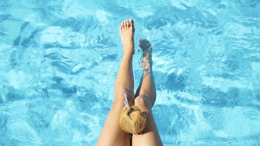The female legs splashing in pool. Young girl | Shutterstock HD Video #1022851339