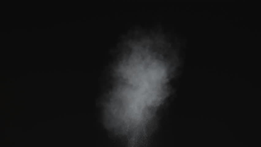 Dusty bullet hits on a wall with chunks of debris flying out .  Powder explosion on black background. Impact  dust particles. Dust explosion in front of black background, slow-motion close up. VFX