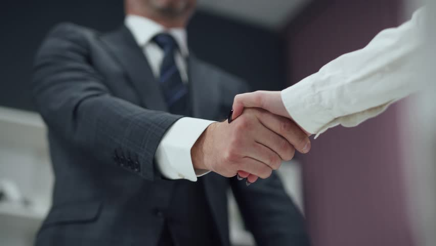 Hiring, man in a suit, a businessman shaking hands with a woman colleague, a handshake in the office. #1022870026