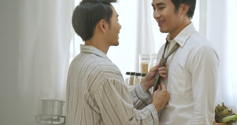 Lovely gay couple, man helps to put on a tie for his boyfriend. In slow motion. People with gay, homosexual, lifestyle and relationship concept.  #1022872483
