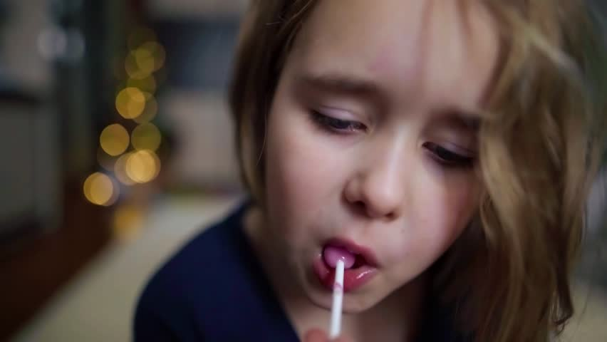 Little girl enjoying Lollipop while looking at camera. Child eats sweets, sweets, sugar | Shutterstock HD Video #1022885368
