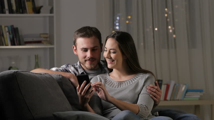 Excited couple finding amazing smart phone content sitting on a couch in the living room at home