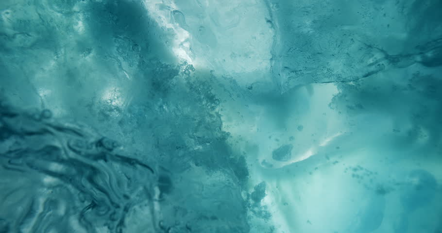 Underwater ice with rising air bubbles. Macro shot of beautiful turquoise underwater ice. #1022909890