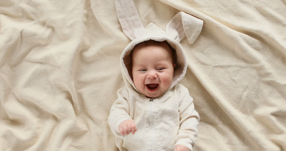 Cute baby smiling and looking in the camera close up. Little kid in Easter bunny costume, top view