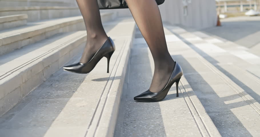 Close up slow motion of business woman walking up on stairs in city street with laptop bag