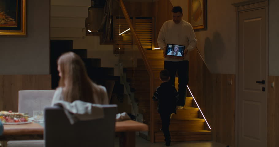 Senior man grandfather having a video call with his daughter during thanksgiving dinner, happy family greeting a remote guest. 4K UHD 60 FPS SLOW MOTION Blackmagic RAW