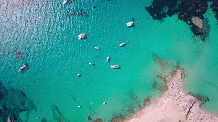 Flying in a circle above beautiful bay on Ibiza with beach, yachts and clear blue sea 4K