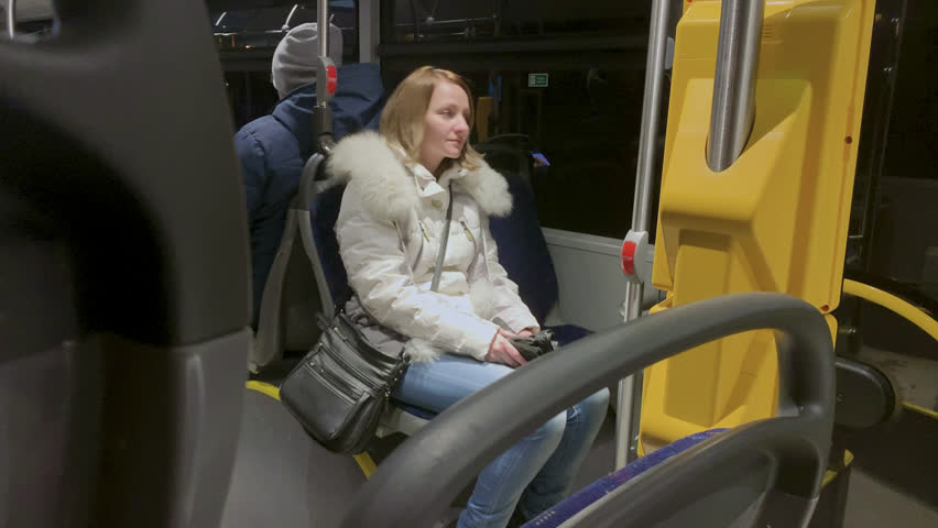 Young Woman in winter clothes in a City Bus. Passenger at Back of Bus. Beautiful girl traveling by bus at night. | Shutterstock HD Video #1022934463