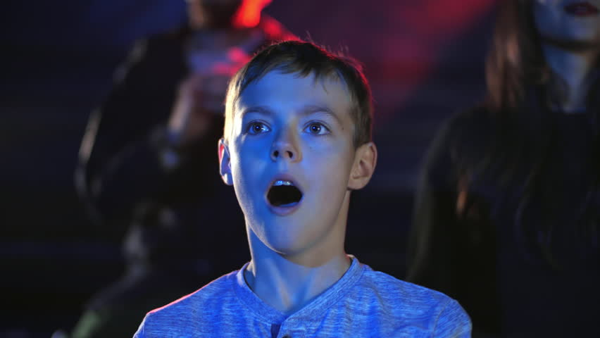 Satisfied surprised boy in projector lights clap hands in circus to the artists, enjoying gladness after dangerous aerial acrobatic action and impressions magic show. Emotional concept at premiere | Shutterstock HD Video #1022939647