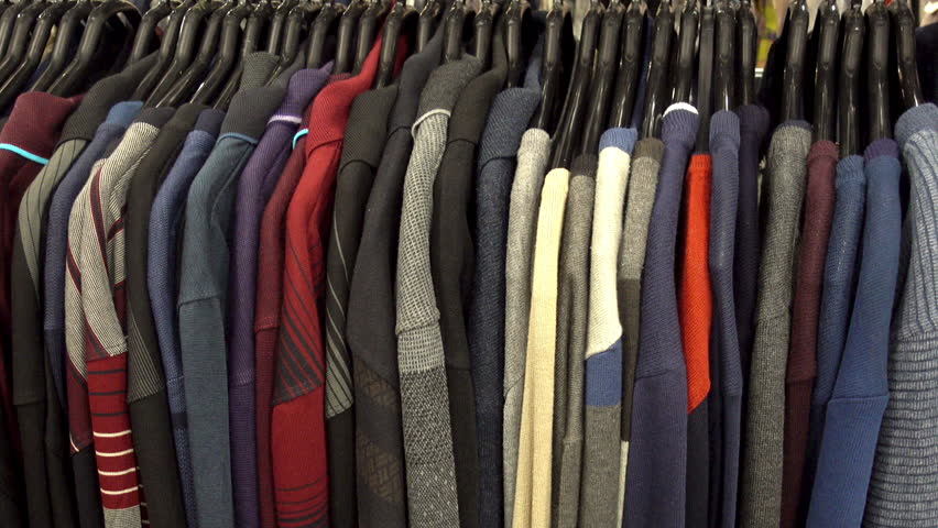 Fashionable collection of warm clothes. Various sweaters hang on hangers on the rack. HD video | Shutterstock HD Video #1022971597