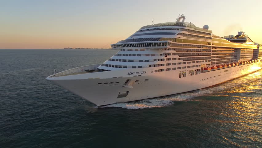 Miami, USA – January 19, 2019: Aerial drone view of large cruise ship leaving Miami harbor, sailing at sea during sunset, warm orange and red color