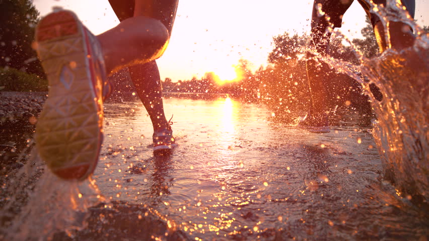 SLOW MOTION TIME WARP, SUN FLARE, CLOSE UP: Fit training partners run in refreshing river water towards beautiful summer sunset. Glassy drops of water fly as young couple jogs through serene nature.