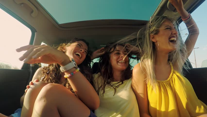 Three female friends enjoying traveling in the car. Sitting in rear seat and having fun on a road trip. #1022988568