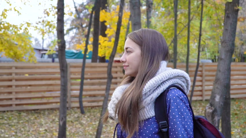 Beautiful young woman wears knitted scarf and walking in autumn park. 4k video motion | Shutterstock HD Video #1022998045