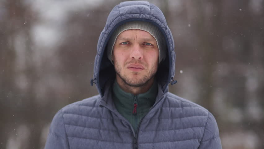 Portrait of a young handsome man in a hood on the background of winter cold forest | Shutterstock HD Video #1022998867