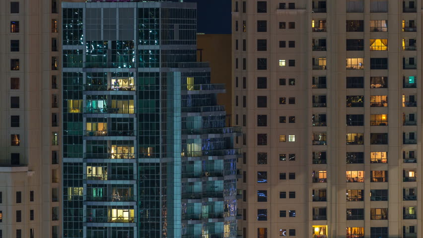 Glowing windows in multistory modern glass residential building light up at night timelapse. People in apartments. Skyscrapers illuminated at evening. Dubai Marina and JBR, UAE. | Shutterstock HD Video #1022999677
