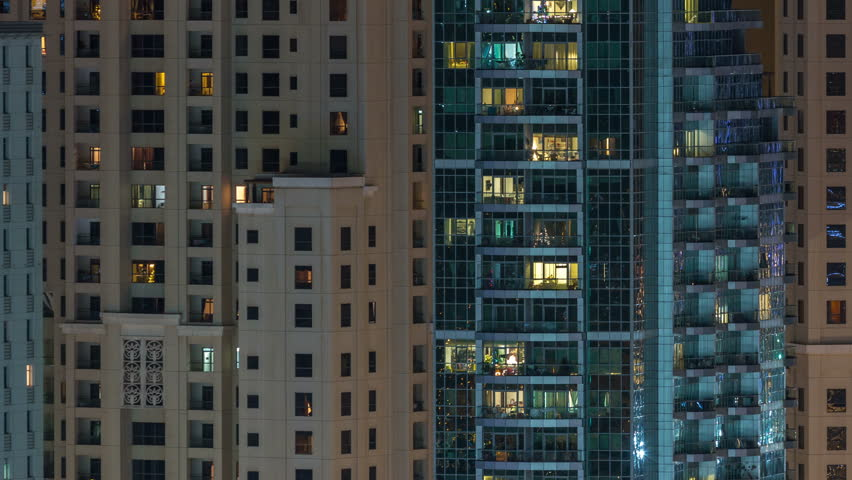 Glowing windows in multistory modern glass residential building light up at night timelapse. People in apartments. Skyscrapers illuminated at evening. Dubai Marina and JBR, UAE. | Shutterstock HD Video #1022999686