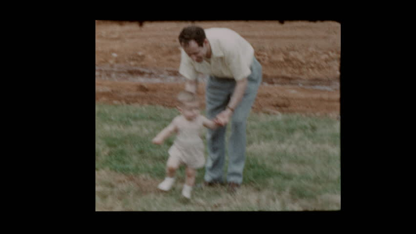 1954 Father lifts and carries toddler son by one arm