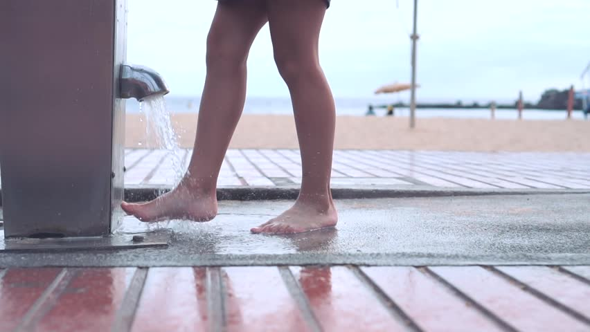 Little girl in dress washes his feet from the sand near the sandy beach in a foot shower. Legs close up view #1023013264