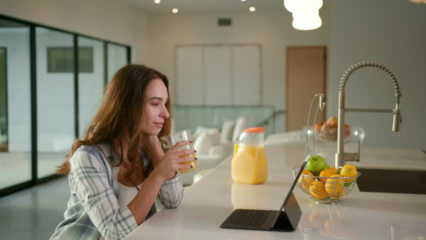 Woman drinking an orange juice at modern kitchen in contemporary house