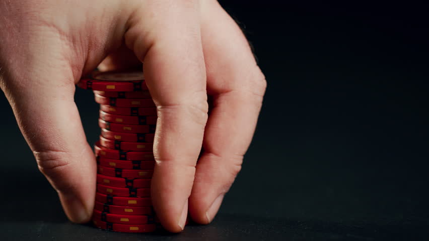 A stack of red poker chips slides in on a black background. At the end the hand takes them away.  | Shutterstock HD Video #1023020572