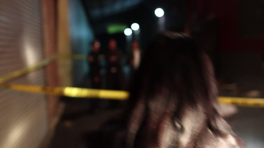 Medium close-up steadicam shot follows behind a female detective as she lifts up a police line and enters a crime scene. Other detectives and police can be seen out of focus in the background.