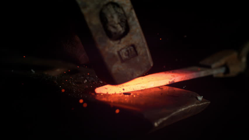 SUPER SLOW MOTION, MACRO, DOF: Red hot piece of metal is being held by tongs and struck by a big hammer. Glowing particles flying away from a knife blade being manufactured by experienced bladesmith. | Shutterstock HD Video #1023034690