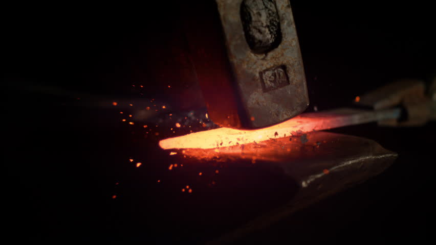 SLOW MOTION, MACRO, DOF: Small black particles flying away from hot red blade while getting forged by an unrecognizable blacksmith. Glowing piece of iron being forged into blade. Forging knife blades.