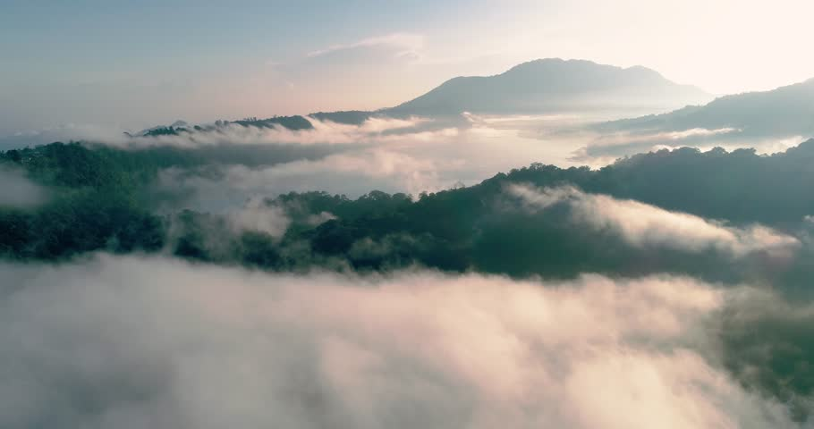 Aerial top shot drone falls into the clouds flying at dawn over the mountains and lake 4K #1023036601