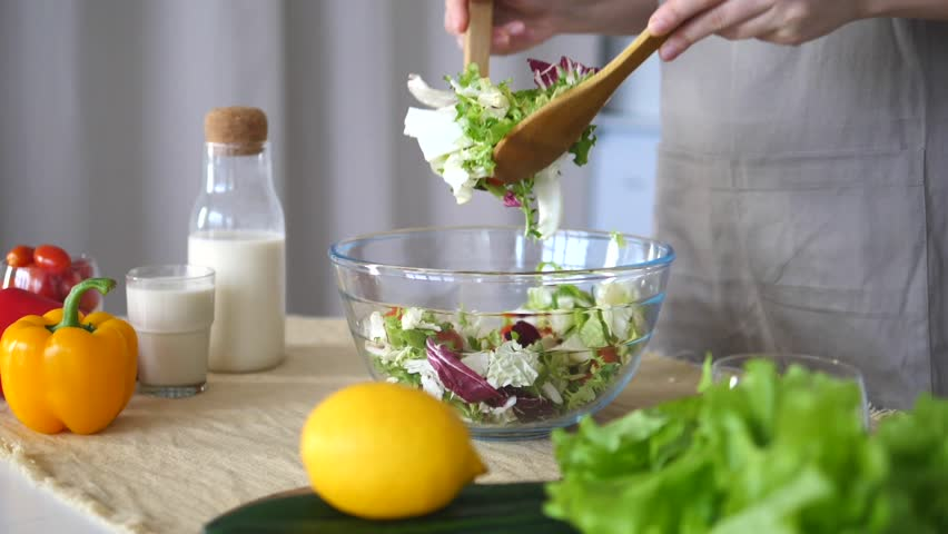 Closeup Of Female Hands Mixing Green Salad In A Bowl At Kitchen.