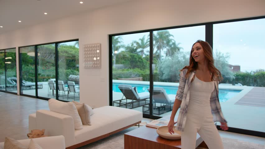 Woman walking into a huge modern contemporary home that she rented for a vacation, she is amazed about it