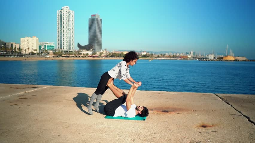 Beautiful couple practicing acro yoga in the morning outdoors near the sea. Balance and connection concept. slowmotion shot | Shutterstock HD Video #1023061639