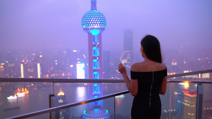 Elegant asian woman in gown drinking white wine glass at rooftop bar terrace looking at city lights skyline view of Shanghai sunset. Luxury travel or high end lifestyle nightlife and going out. China