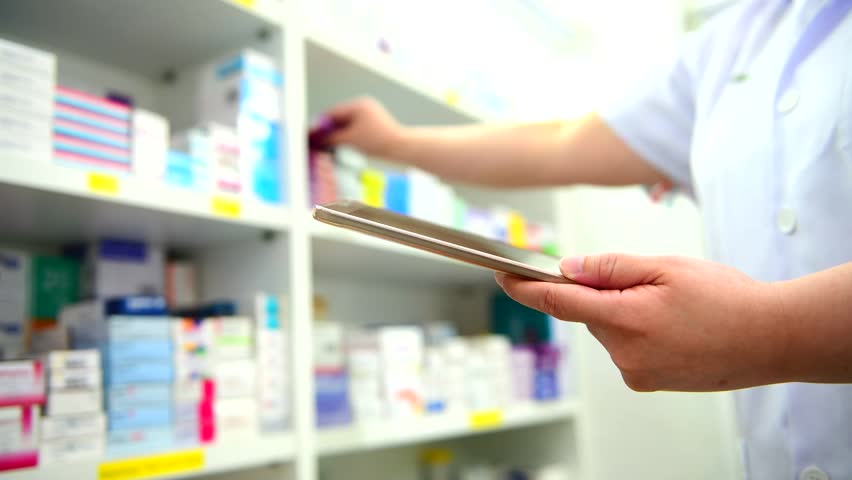 Pharmacist holding computer tablet using for checking medication details on a box in pharmacy drugstore.