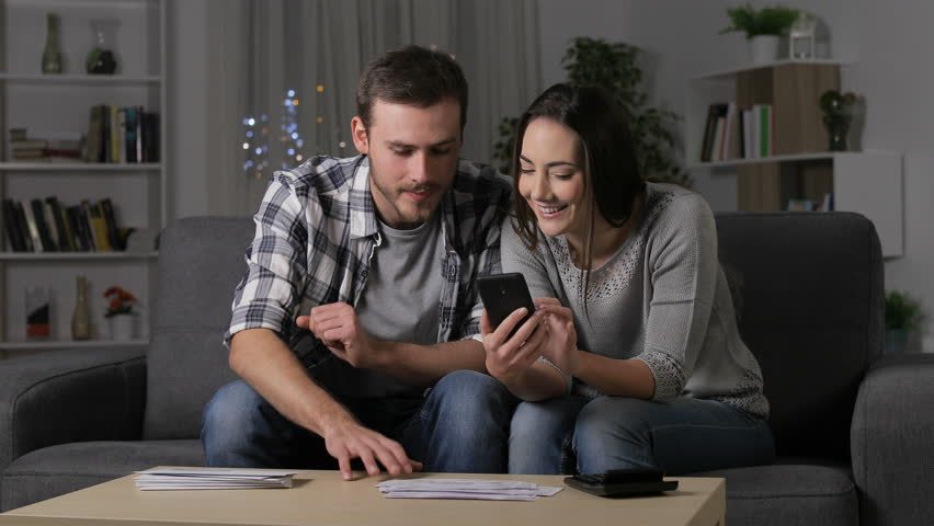 Happy couple comparing receipts online on smart phone sitting on a couch in the night at home Royalty-Free Stock Footage #1023078328