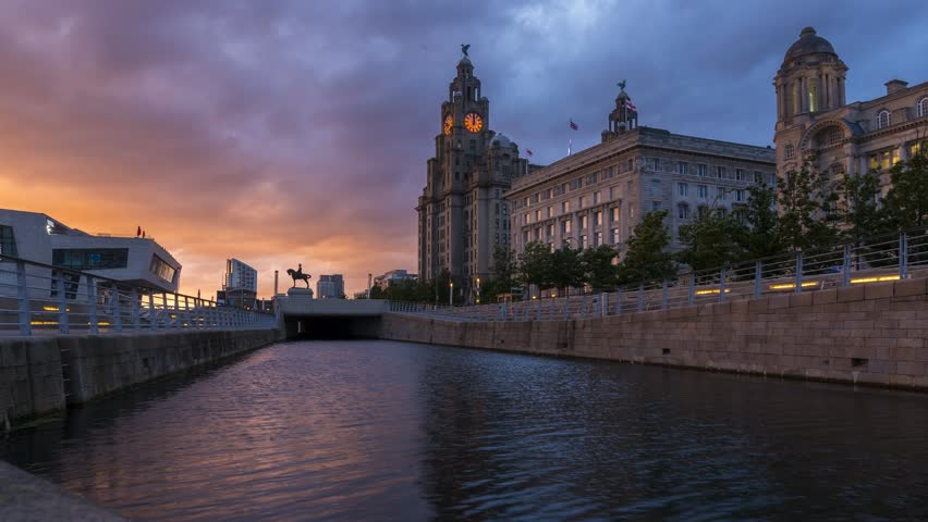 Liverpool / United Kingdom - June 11 2017: A timelapse video with sunset at the Liverpool canal link with the Pier Head Ferry Terminal and the Royal Liver Building