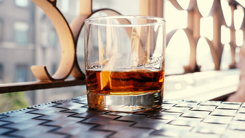 Pouring old whiskey into a glass with some ice cubes and beautiful light reflexions | Shutterstock HD Video #1023094408