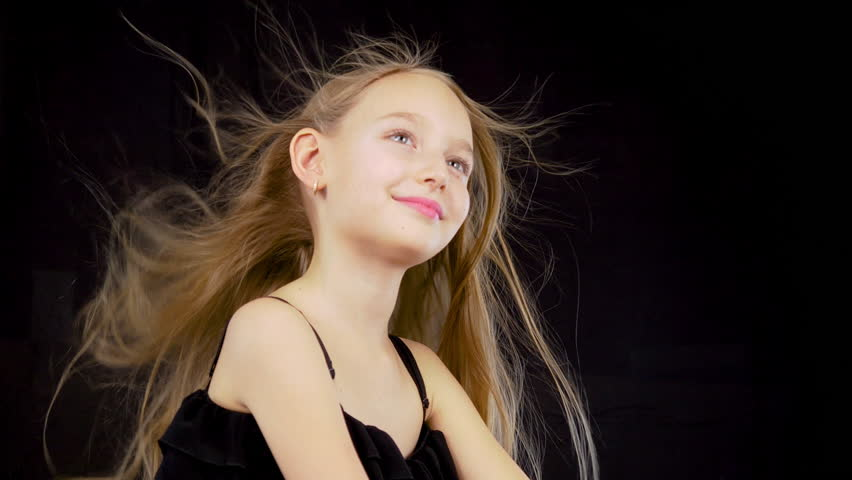 Cute girl with fluttering hair. Close up little model girl with fluttering hair isolated on black background. Wind concept