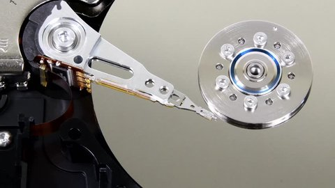 Computer hard drive with cover removed showing internal components. Shows drive head moving across the disk.