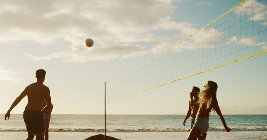 Active friends playing beach volleyball at sunset, cinematic slow motion golden light | Shutterstock HD Video #1023104593