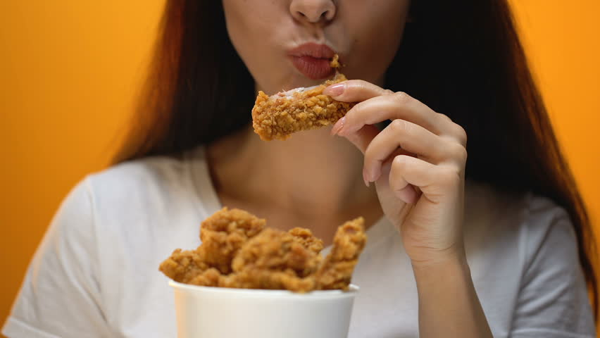 Girl eating chicken wings, high calorie food and health risks, cholesterol #1023107221