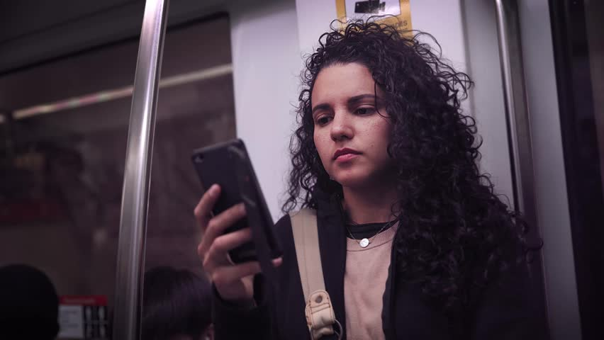 Hispanic young woman using mobile phone while traveling in the train or subway. Madrid, Spain