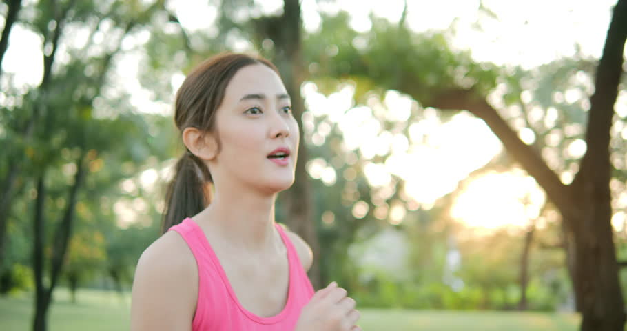 Asian Beautiful Woman Running in the Sunny City Park Exercising Outdoors. Healthy Lifestyle Concept.