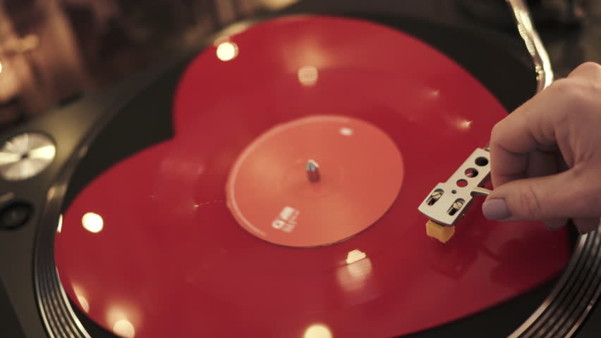 Varna, Bulgaria - January 2019, turntable Numark: hand girl DJ red heart-shaped vinyl record puts stylus bright background bokeh of lights. Valentine's Day. Love. Popular Disco Trends 70s, 80s, 90s