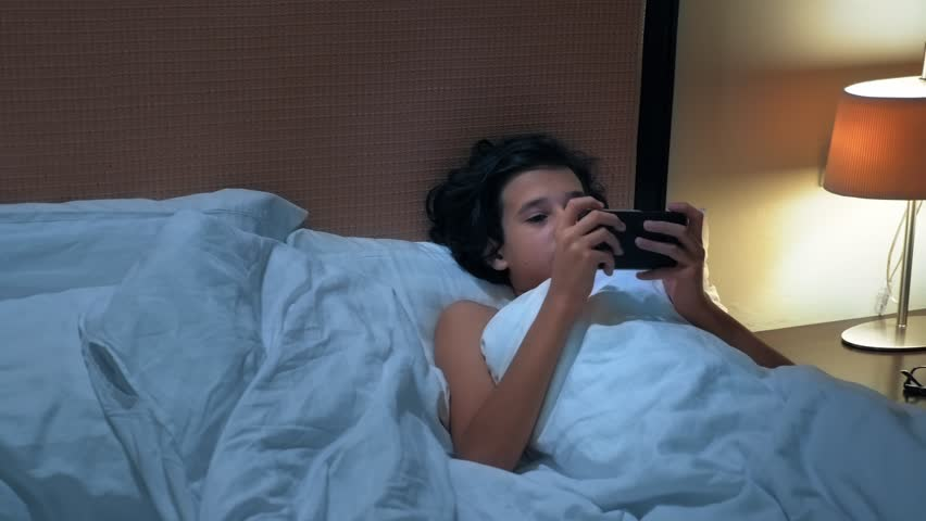 Teen boy uses smartphone on bed before sleep at night. Mobile addict concept.   Shutterstock HD Video #1023133441