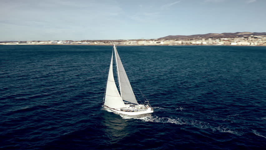 Aerial view of unknown sailboat cruising at sea | Shutterstock HD Video #1023135208