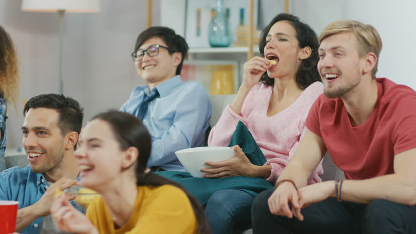 At Home Diverse Group Friends Watching TV Together, Eating Snacks and Drinking Beverage. Watching Comedy Sitcom or a Movie, Laughing and Having Fun Together. #1023137800