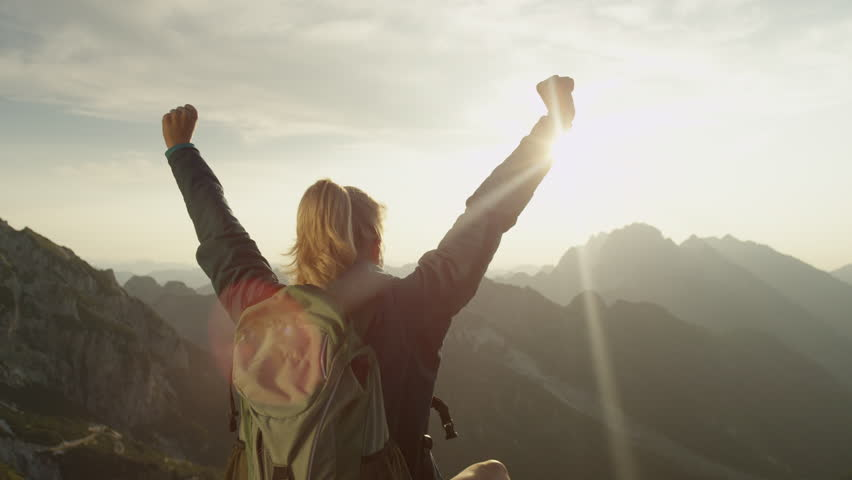 SLOW MOTION, CLOSE UP, LENS FLARE: Trekker girl celebrates reaching the mountaintop with a breathtaking view of the mountain range on a sunny summer day. Unrecognizable hiker woman outstretches arms.