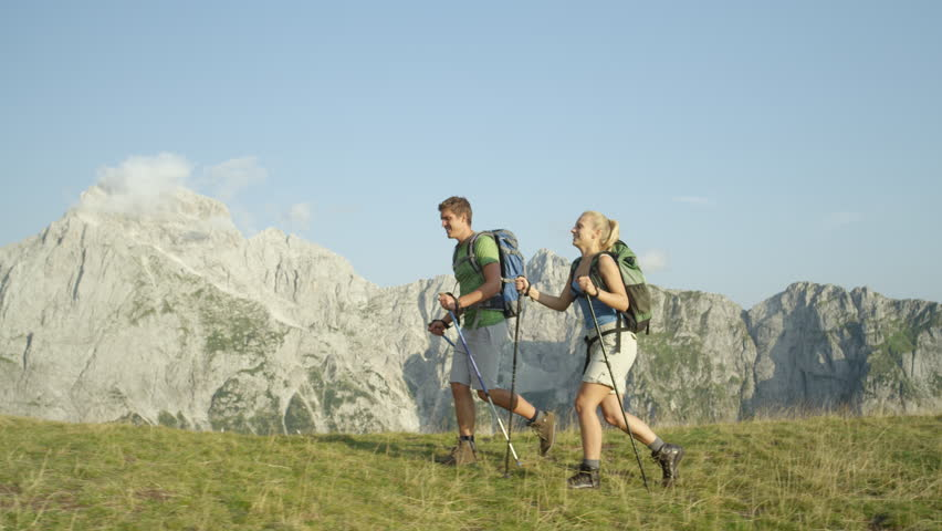SLOW MOTION: Happy tourist couple hiking in the breathtaking Slovenian mountains during their active summer vacation. Cheerful young trekkers enjoying the view of the scenic Alps during their ascent. | Shutterstock HD Video #1023163945