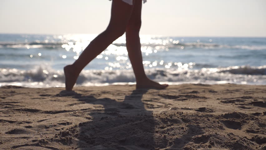 Female feet walking at the sea beach on a sunny day with waves at background. Legs of young woman stepping at the sand. Summer vacation or holiday concept. Side view Slow motion Close up #1023169252